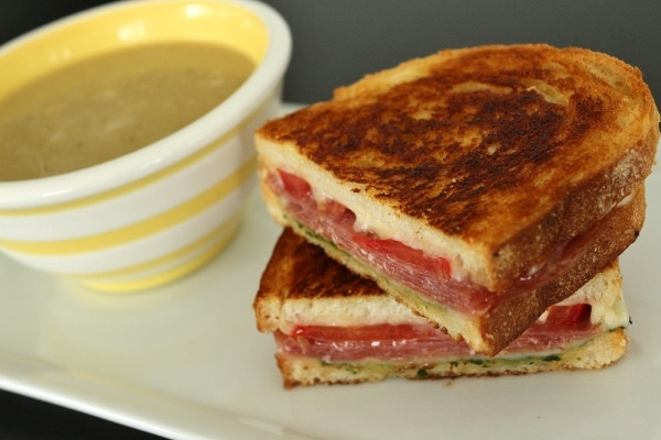 An Italian grilled cheese with salami, tomato, and pesto on a white plate with a cup of soup in a white and yellow striped bowl.