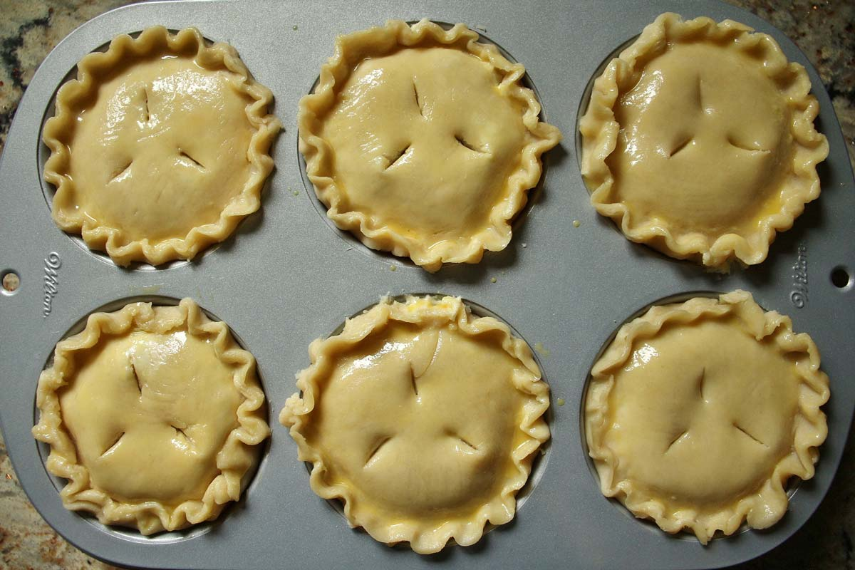 6 small pies assembled in a jumbo muffin pan, brushed with egg wash.