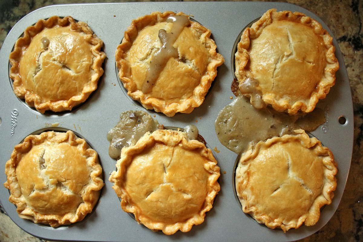 6 small pies assembled in a jumbo muffin pan, baked and golden with juices bubbling out.