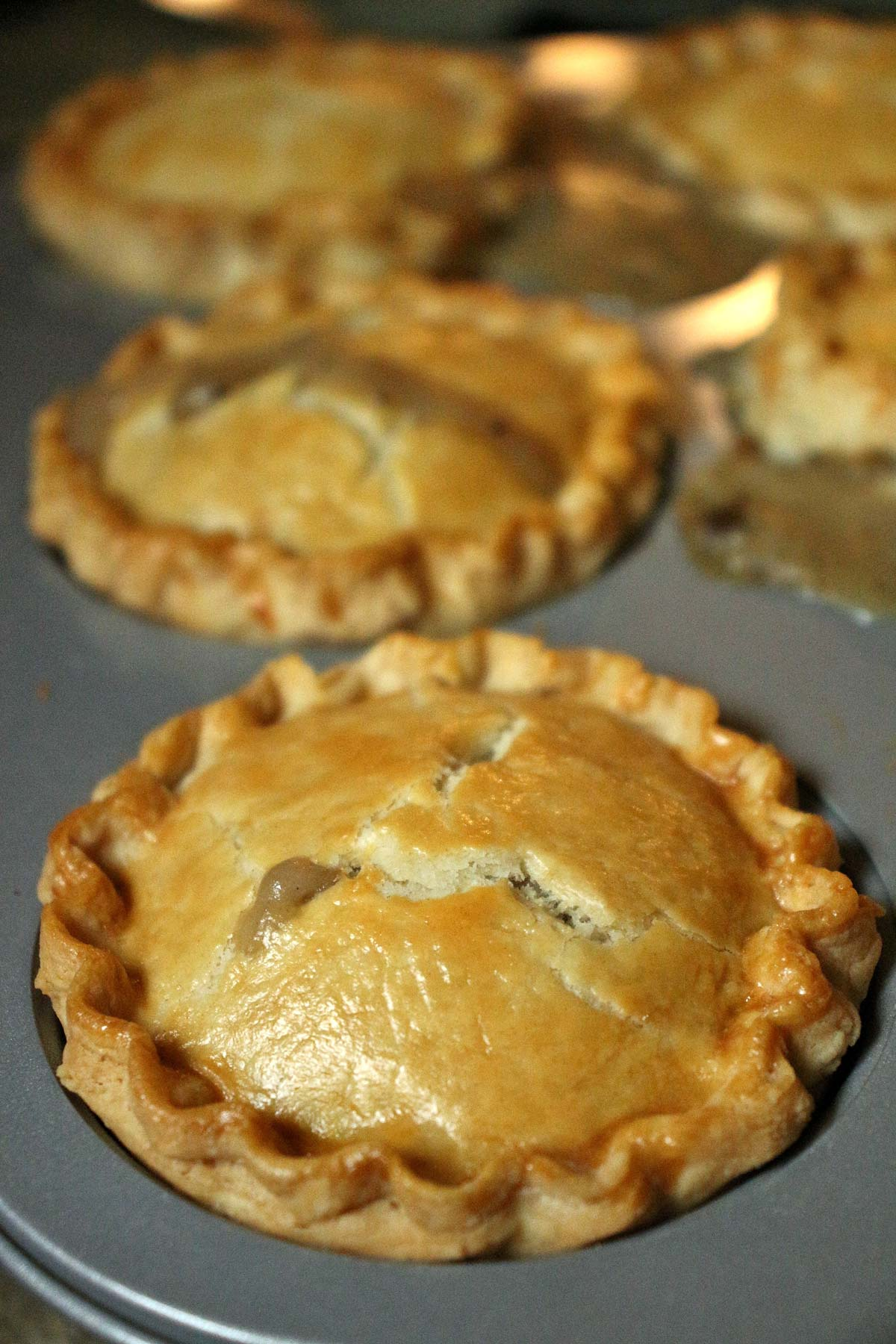 Individual chicken and mushroom pies baked in a jumbo muffin pan until golden and bubbly.
