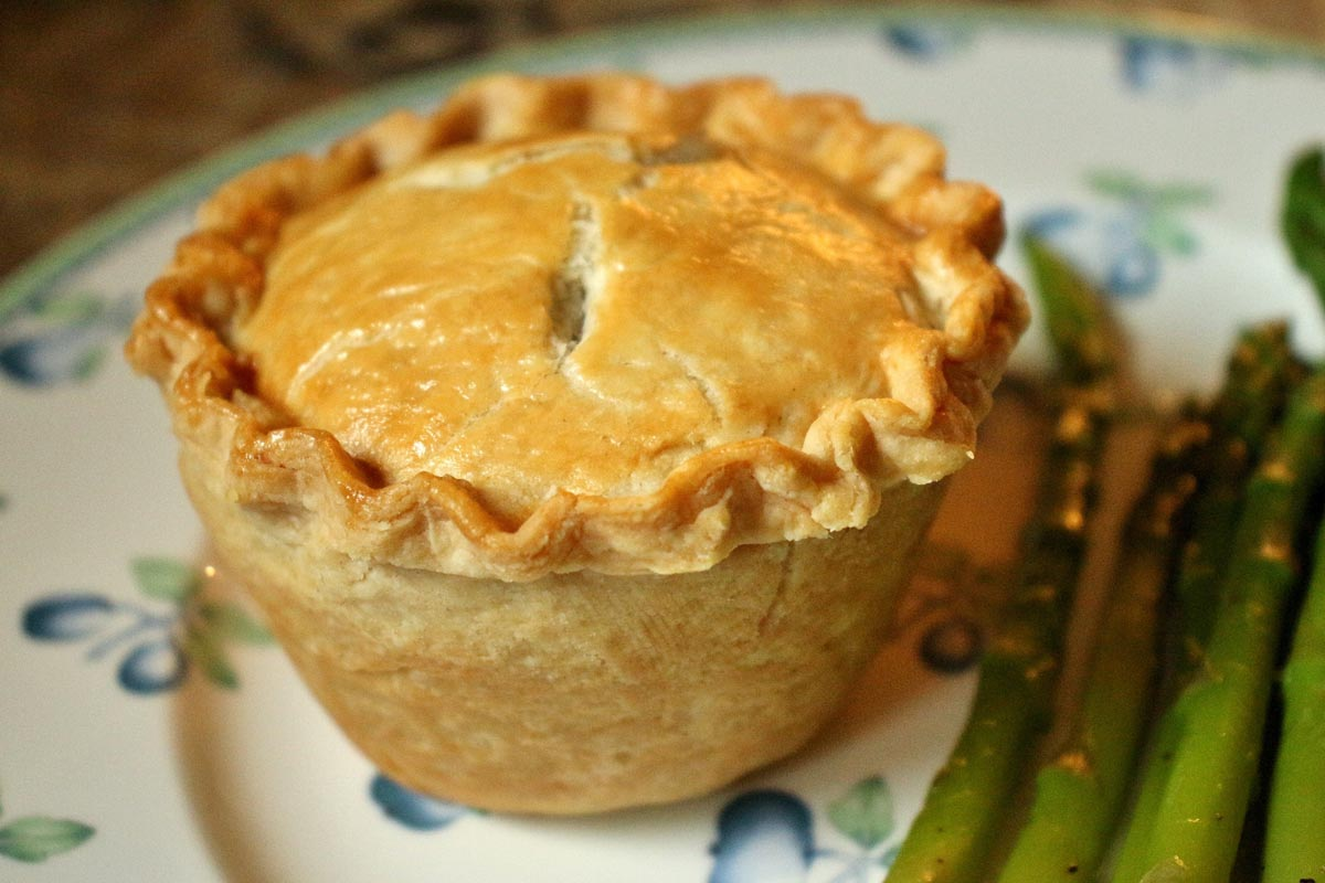 A small chicken and mushroom pie with a golden crust on a plate next to asparagus.