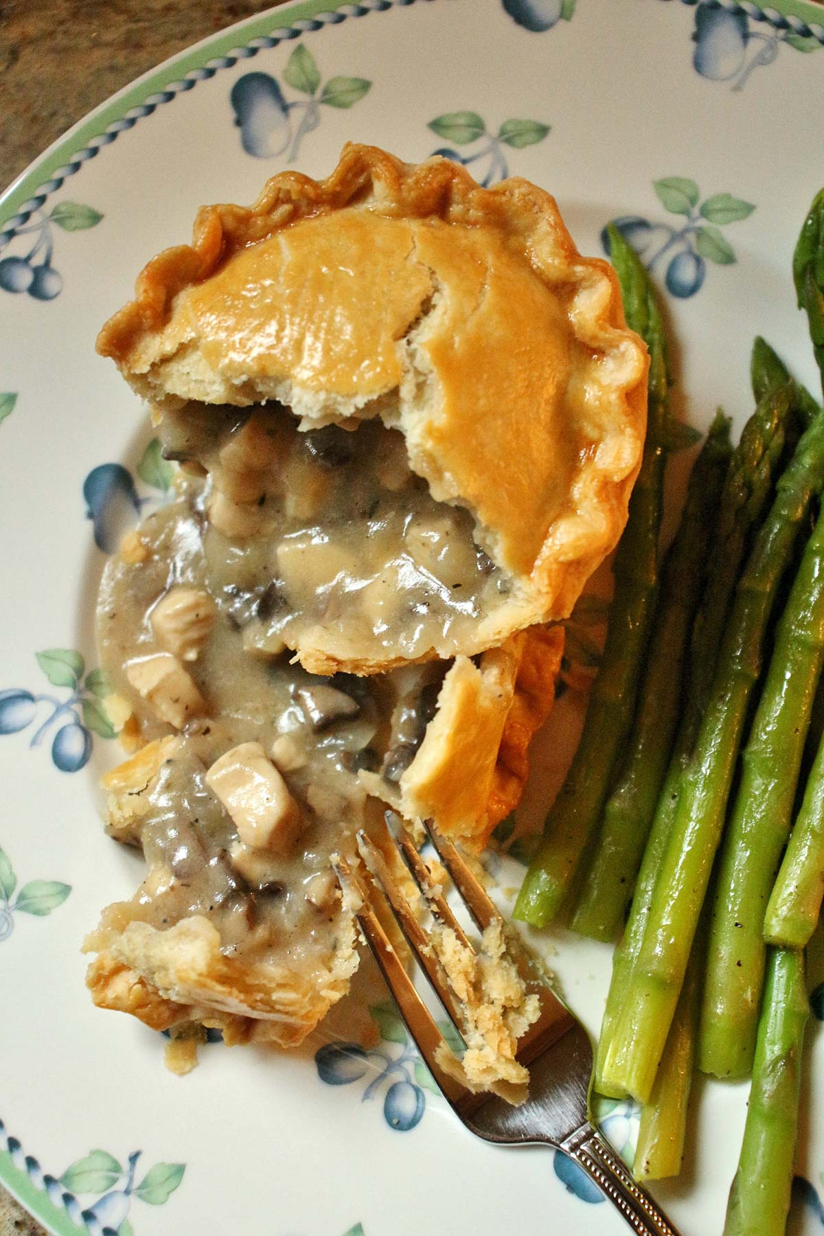 An individual chicken and mushroom pie broken open with the filling spilling out.