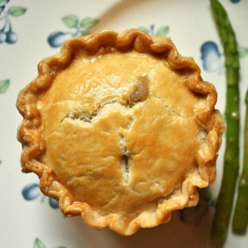 An individual sized savory pie with a golden crust, and asparagus on the side.