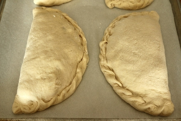 2 unbaked calzones on a baking sheet