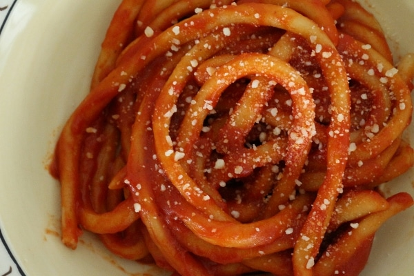 Hand-rolled pici pasta in tomato sauce, topped with grated cheese