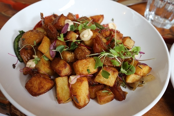 fried cubed potatoes on a white plate