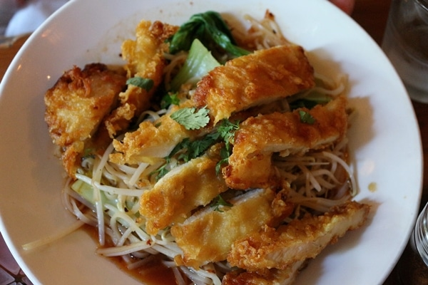 a plate of noodles topped with sliced fried chicken breast
