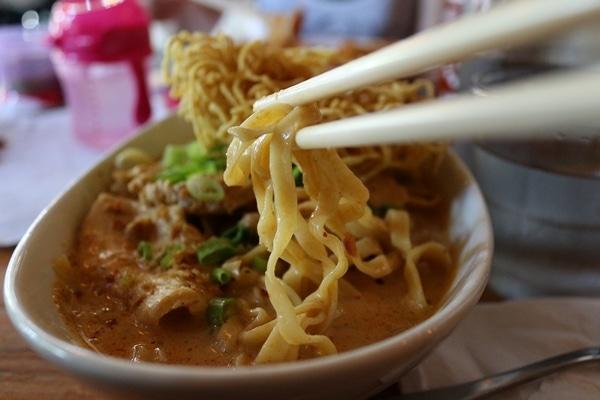 A close up of chopsticks picking up some noodles