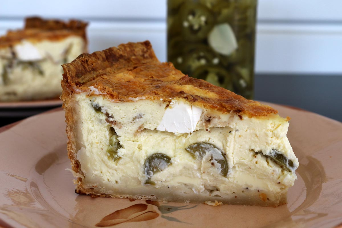 Closeup of a slice of quiche on a plate with jar of pickled jalapenos behind it.