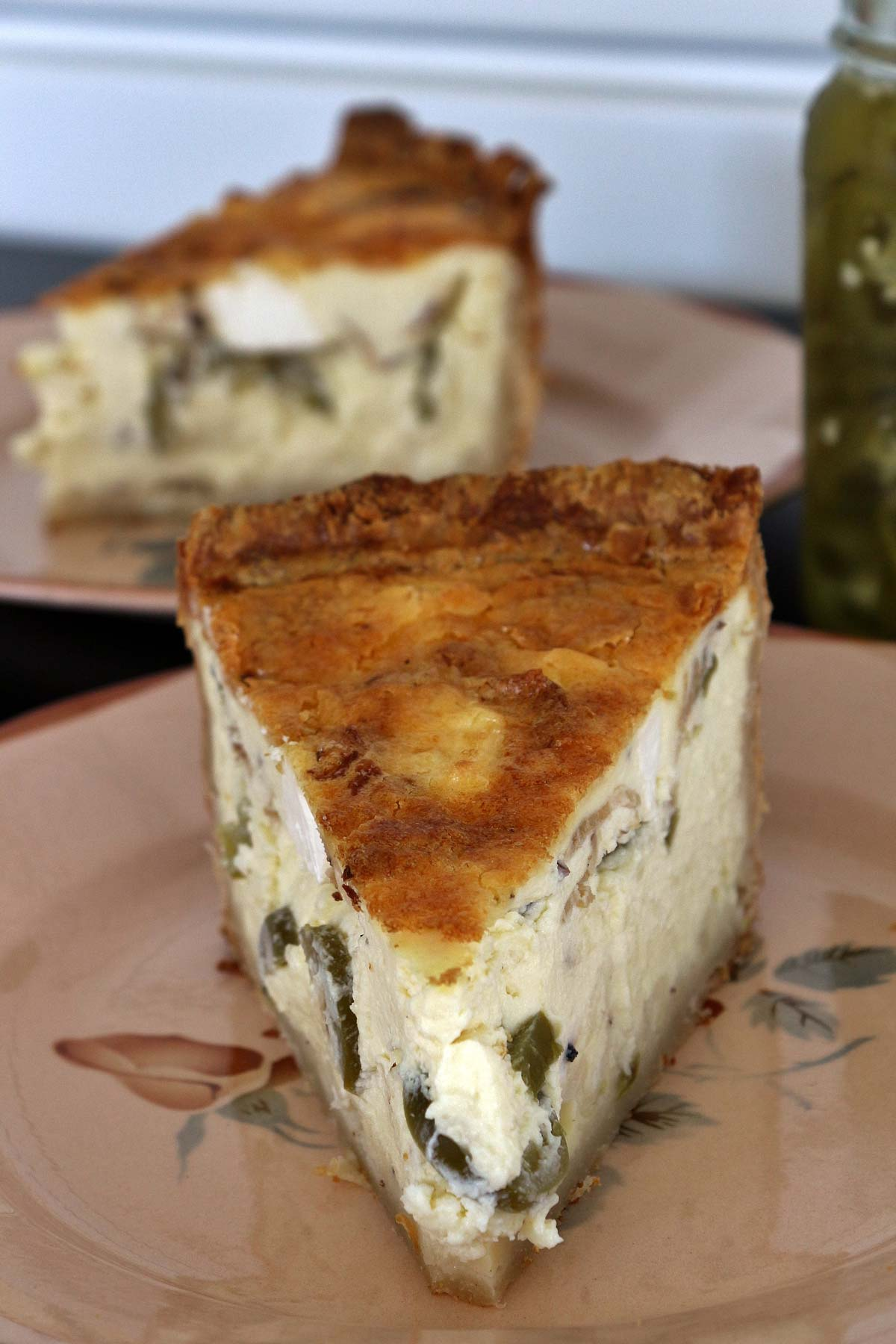 Closeup of a slice of jalapeño popper quiche with another slice in the background.