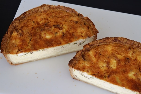Baked quiche cut in half on a cutting board