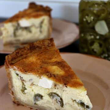 Slice of quiche with pickled jalapenos, bacon and cubes of cream cheese in the filling