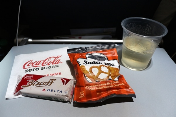 airplane snacks and a drink on a tray table