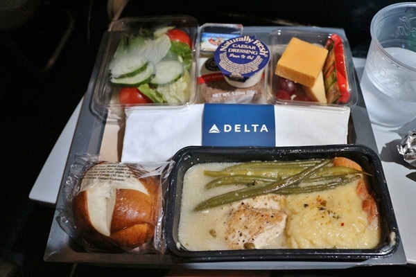 an airplane meal of chicken  with salad