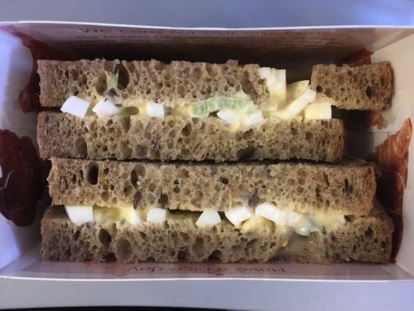closeup of an egg salad sandwich in a box