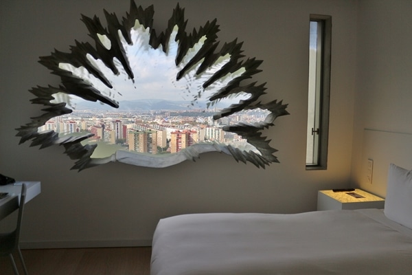 A hotel bedroom with a palm shaped window