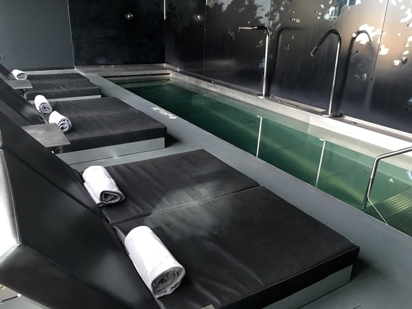A small indoor pool with lounge chairs