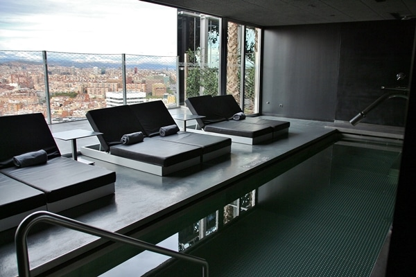 an indoor pool with lounge chairs overlooking Barcelona