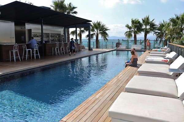 a rooftop hotel pool with lounge chairs and palm trees