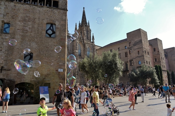 A group of people walking in front of a church with bubbles in the air
