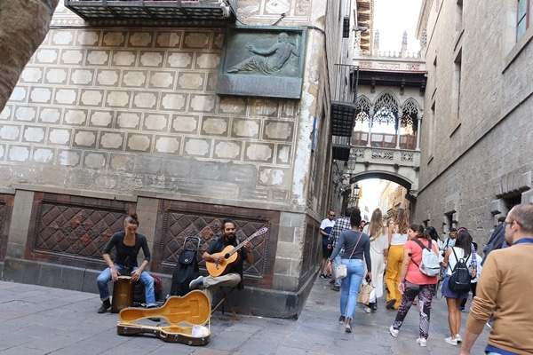 A group of people walking performing music in Barcelona\'s Gothic Quarter