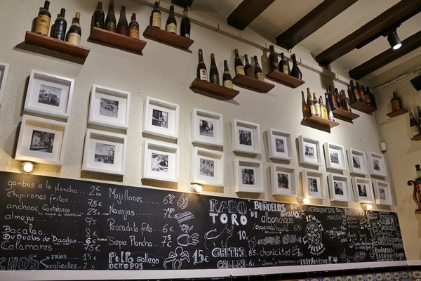 restaurant wall with chalkboard menu, photos, and bottles of wine