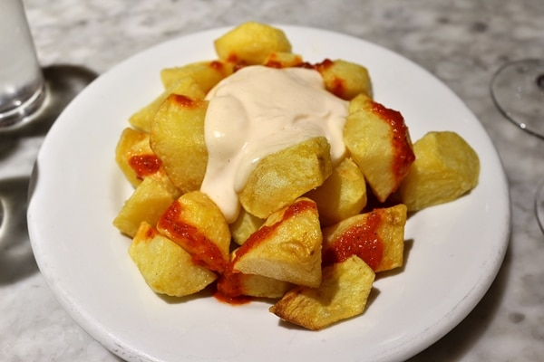 A plate of fried cubed potatoes with red and white sauces on top