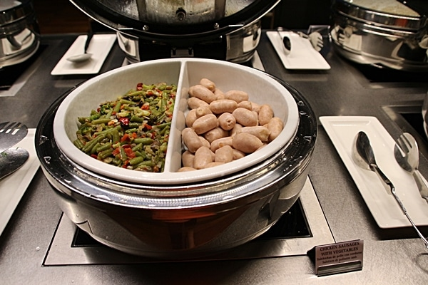 vegetables and sausages on a buffet line