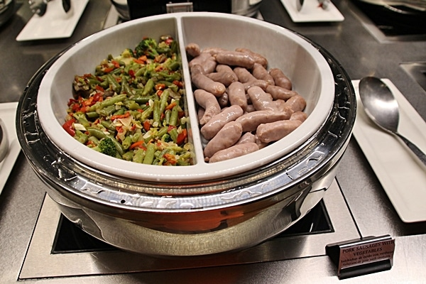 vegetables and small sausages on a buffet line