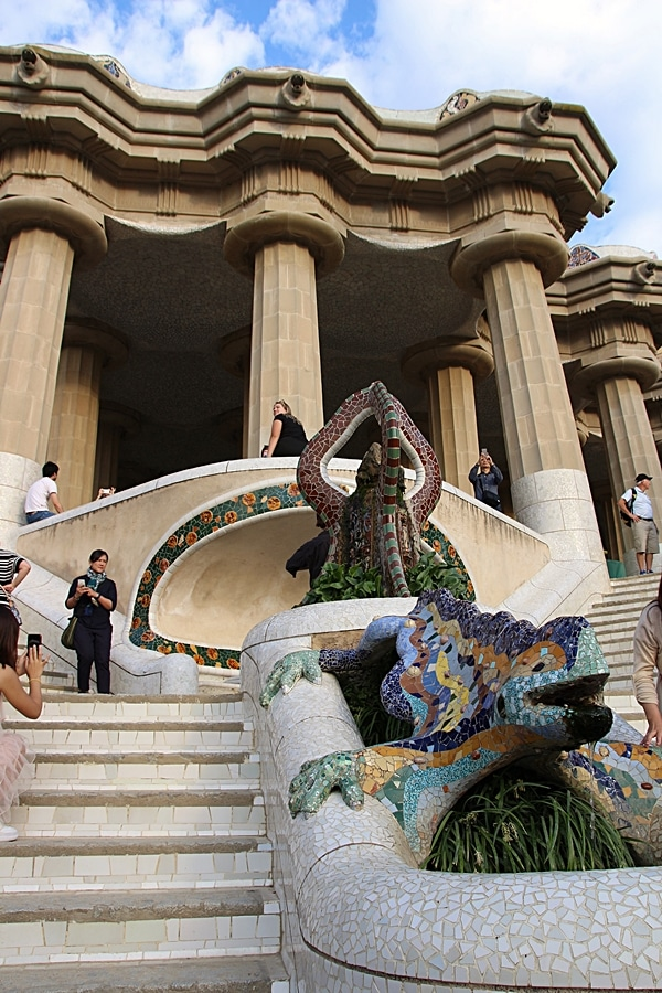 a mosaic lizard statue in front of a building with columns