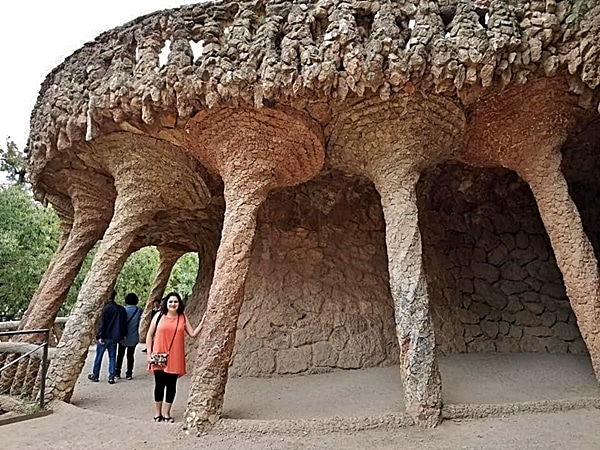 A person standing next to a stone wall with columns in Park Güell