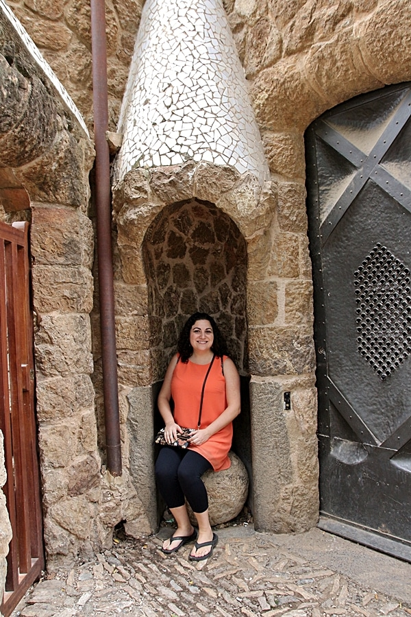 A person sitting in front of a stone building in Park Güell