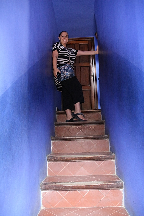 A person standing in a blue stairwell