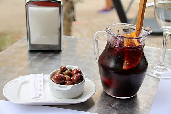 a small glass pitcher of red sangria next to a cup of olives