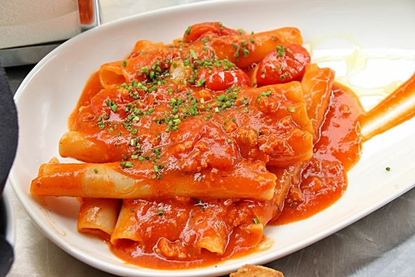 large pasta noodles in tomato sauce on a white plate