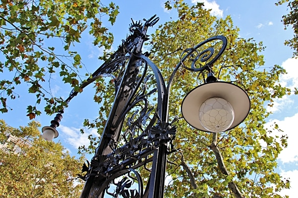 closeup of a fancy street light beneath some trees