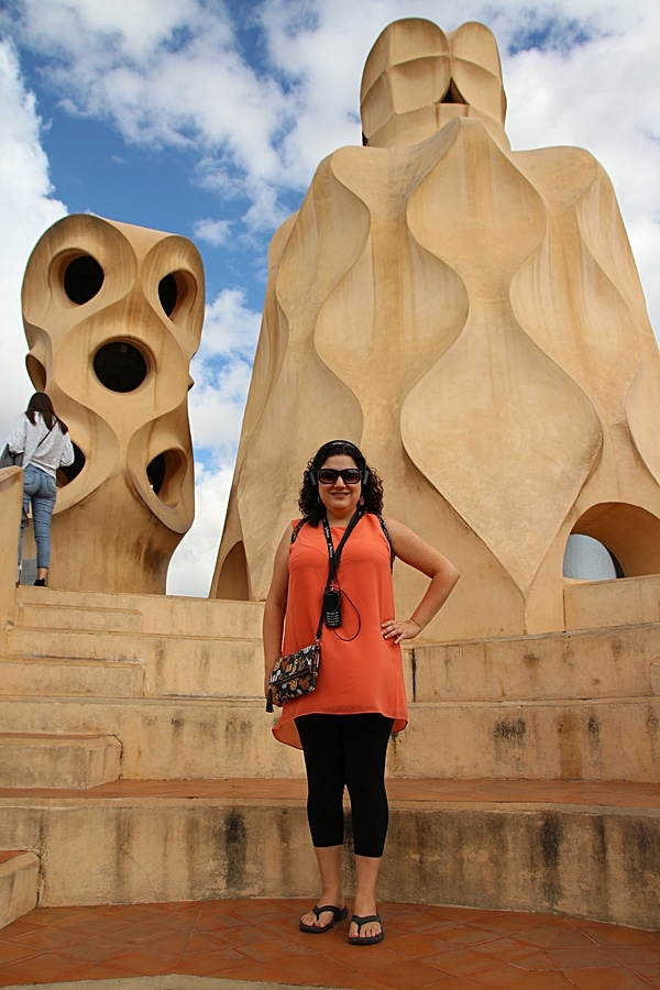 A woman standing in front of a stone chimney on the Casa Milà rooftop