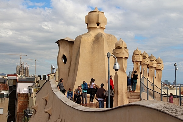 people on the rooftop of Casa Milà with Sagrada Familia in the distance