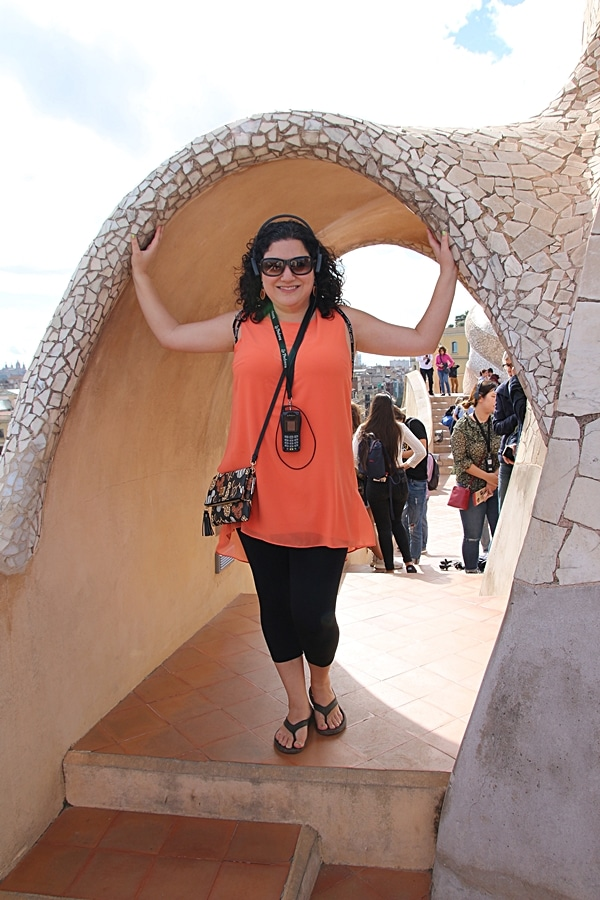 a woman standing under a mosaic archway