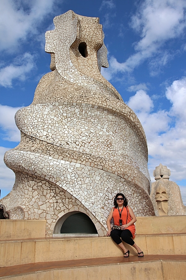 a woman sitting in front of a large mosaic rooftop chimney