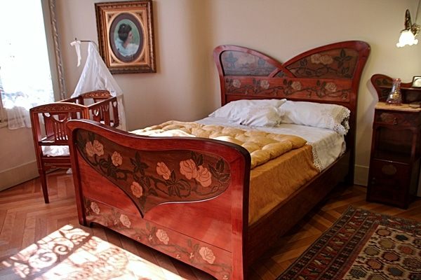 A bedroom with a bed and a crib