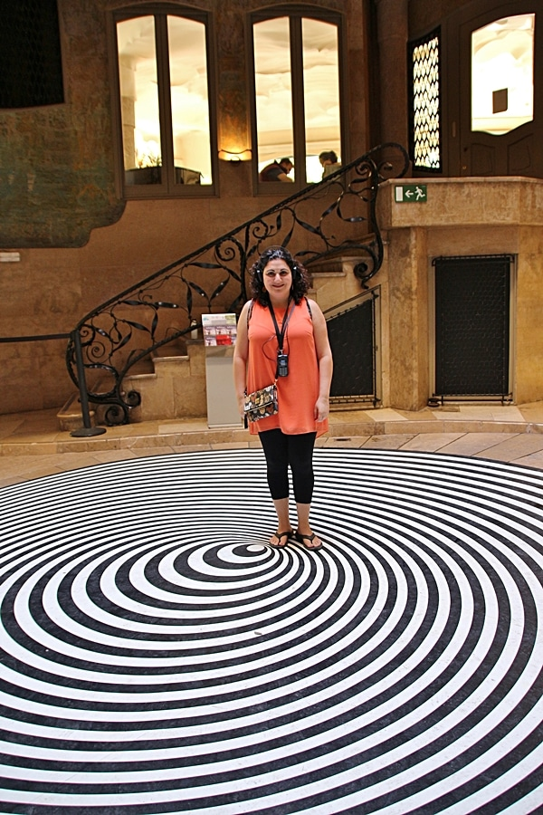 A woman standing on a black and white spiral floor