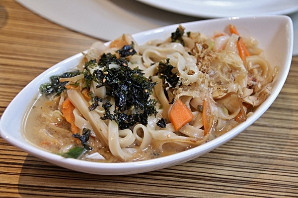 a closeup of rice noodles with broth in an oval dish