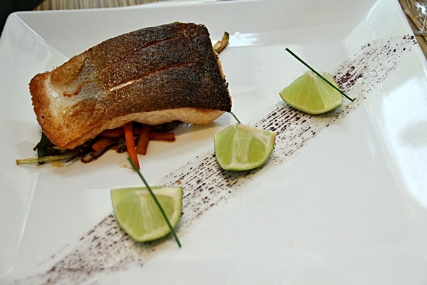 a piece of cooked fish and 3 lime wedges on a white plate