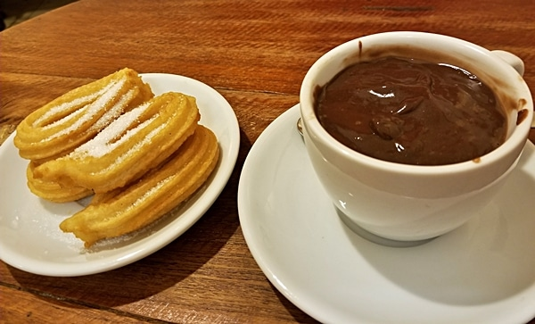 a plate of fried churros next to a cup of hot chocolate for dipping