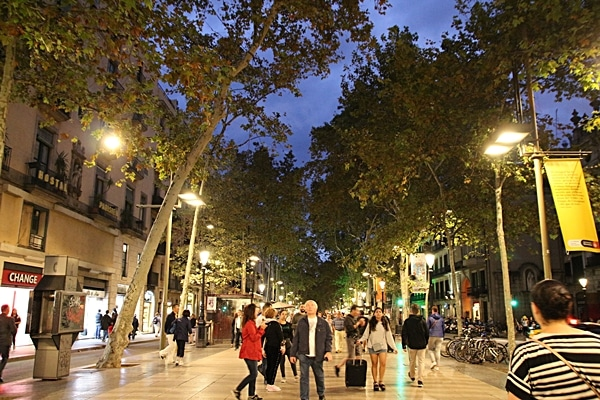 A group of people walking down Las Ramblas in Barcelona at night