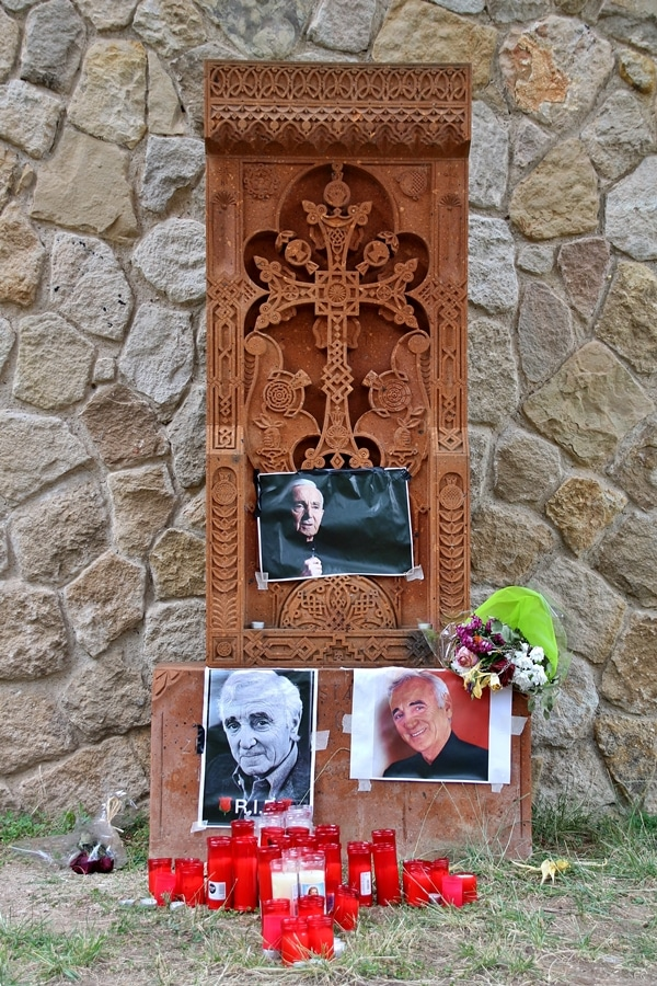 close up of a stone cross with pictures of a man taped to the front