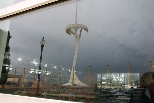reflection of a tall white communications tower in a window