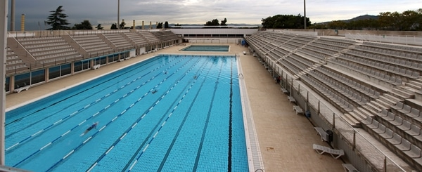 an outdoor Olympic swimming pool with seating on either side