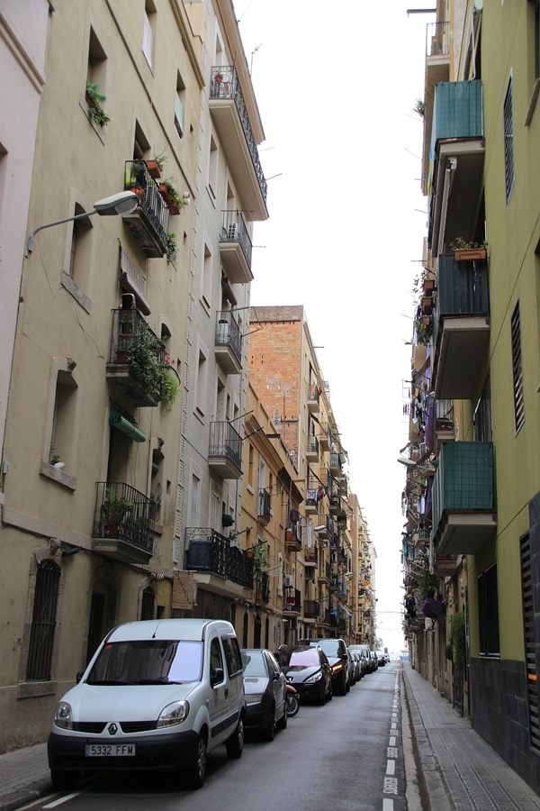 A narrow city street with cars parked on the side of a road